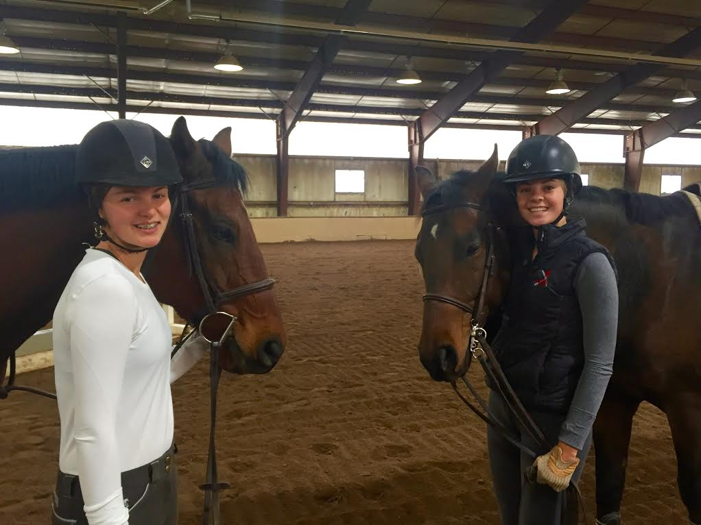 Eloise Clark (left) and Carter Cheo (right) pose with team horses on a Sunday morning, when practices are held.