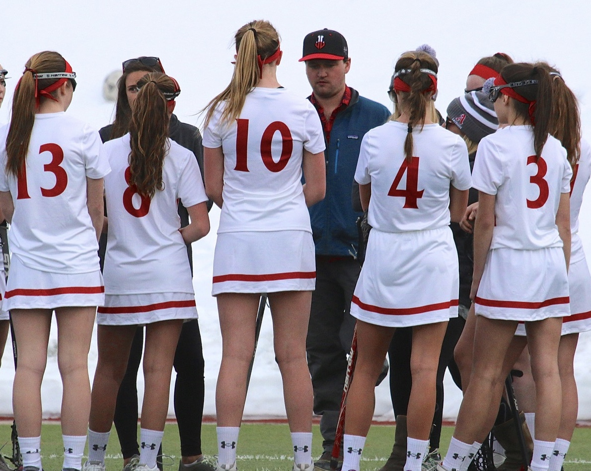 Aspen Girls Lacrosse Team huddling during a game earlier in the season