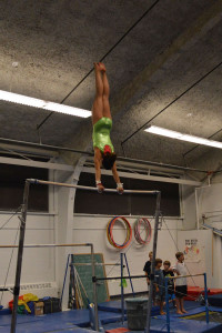 Cheo does giants on the bars during her four hour practice.