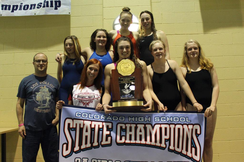 AHS girls swim team poses with banner and trophy