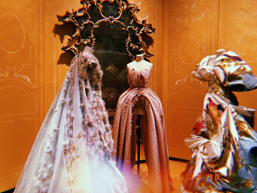 Three delicate ball gowns facing eachother in the