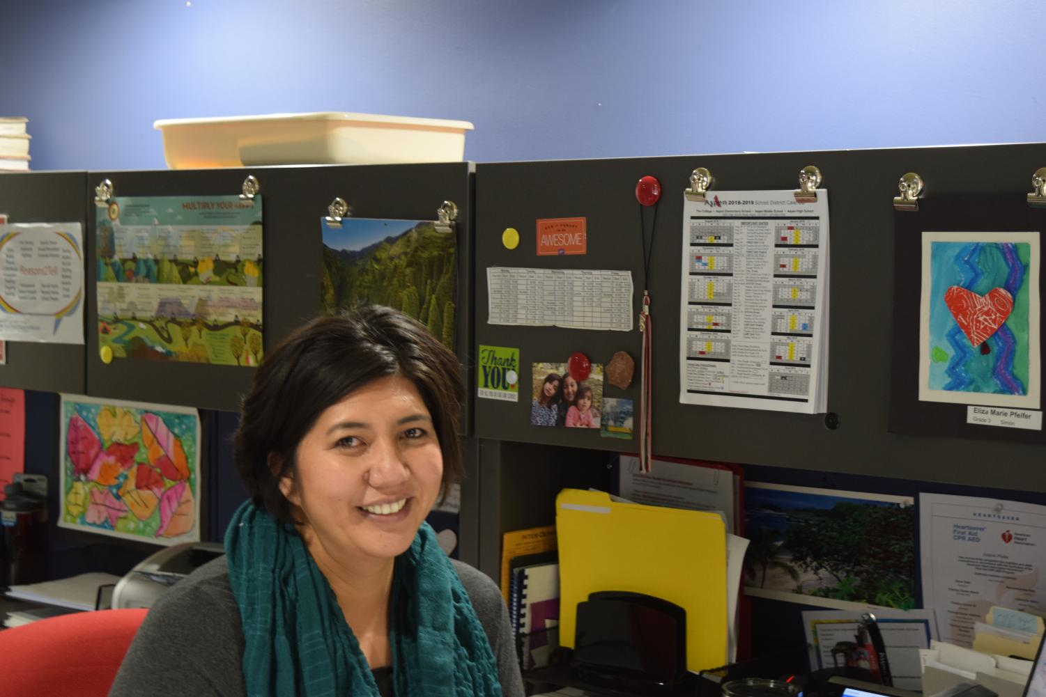 Jolaine Pfeifer smiles at her desk during a busy day at work. Her daughters' art work lines the cabinet behind her.
