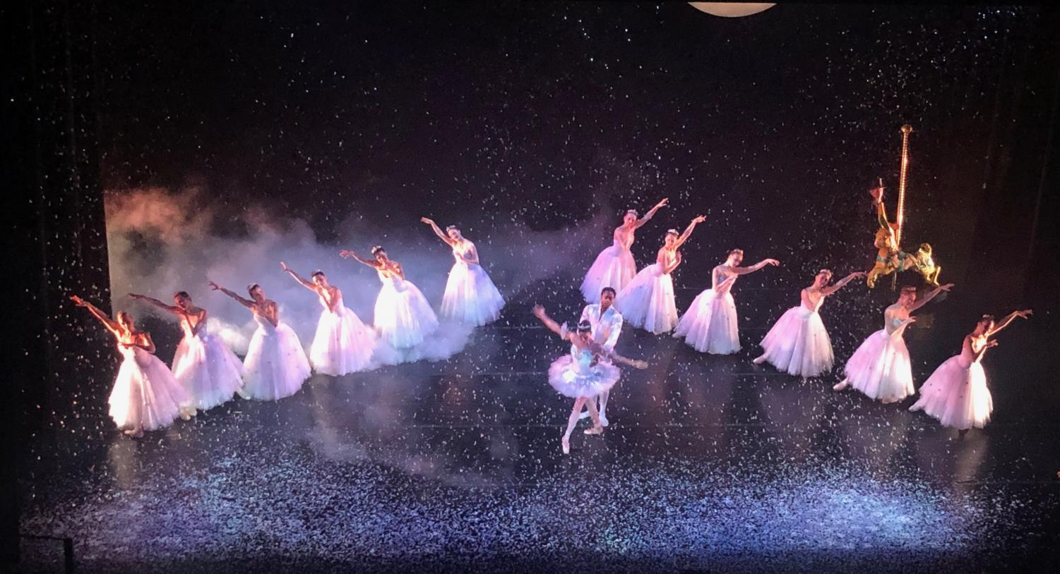 Fake snow falls to create a magical scene as dancers perform the Sugar Plum dance.