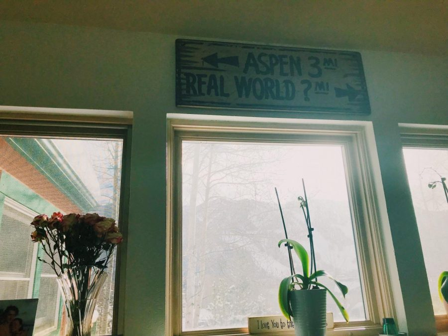A wooden sign hangs above the bright window, Aspen Mountain illuminated in the background. The sign reads,