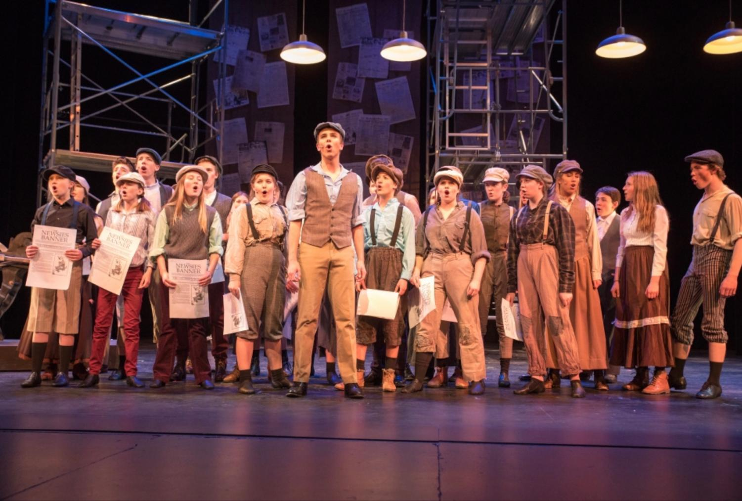 Cast of Newsies stands in the finale after finishing their first show.