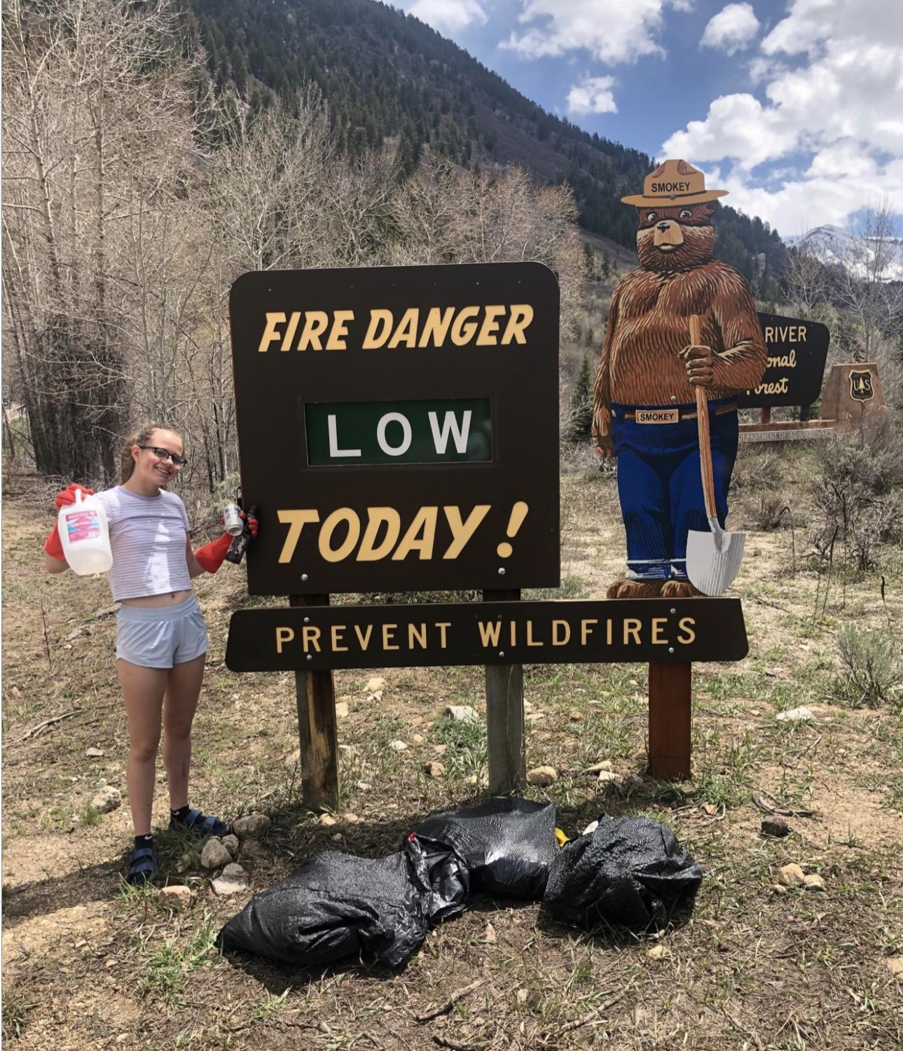 AHS junior, Olivia Burkley, posing next to fire danger sign on Independence Pass during the Guatemala Literacy Club's trash cleanup on May 4, 2019.