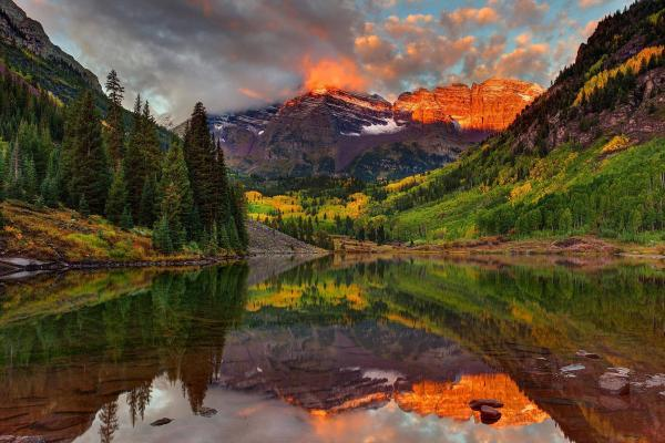 Maroon Bells, one of the most famous places in America to see fall colors, reflects onto Maroon Lake.