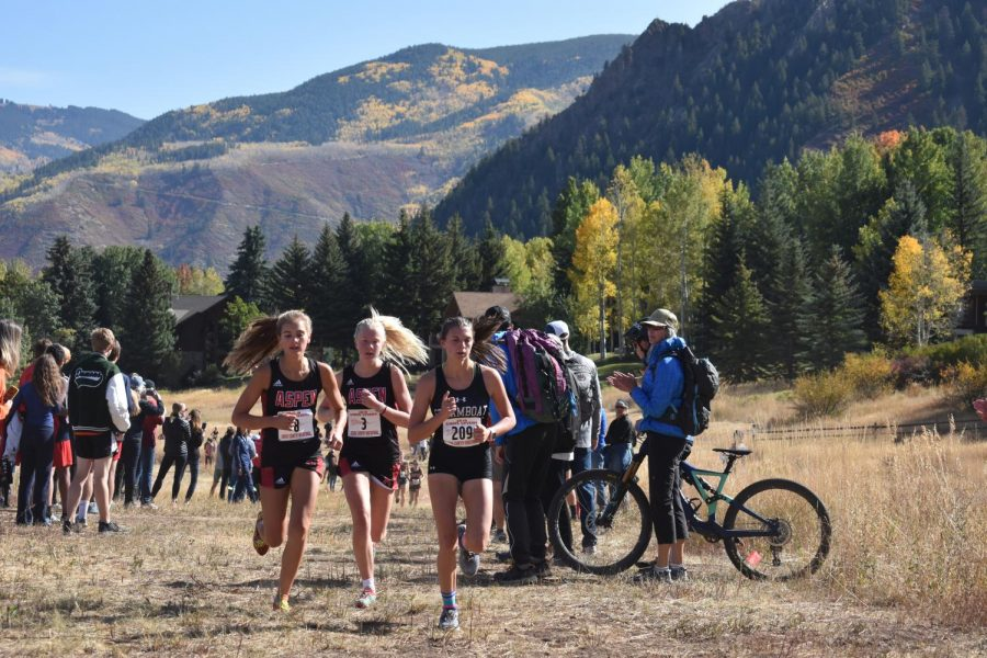 From left to right, Kylie Kenny, Kendall Clark, and a steamboat athlete run side by side during a cross country meet.