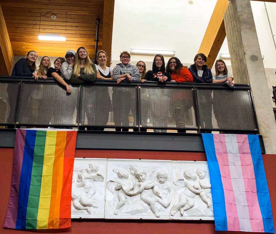 Aspen High School Gay-Straight Alliance club gathers around pride flags hanging in the lobby of AHS.
