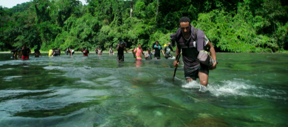 People crossing a river as part of the journey through the Darien Gap.