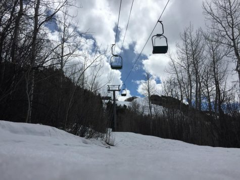 The chairlifts are empty but sled tracks are visible in the mountains.
