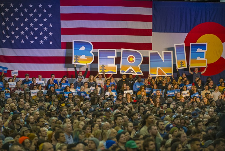 Participants at a rally for Bernie Sanders  in Downtown Denver hold up a sign spelling his name.