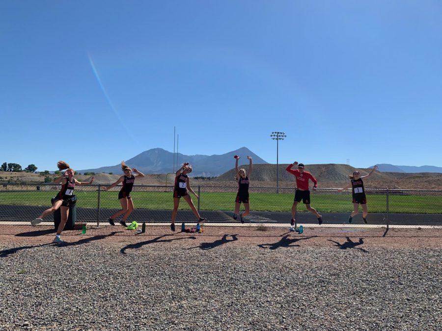 Runners (from left) Edie Sherlock, Stella Sherlock, Kylie Kenny, Michaela Kenny, Coach Chris Keleher, and Macy Hopkinson jump for joy after their Hotchkiss race.
