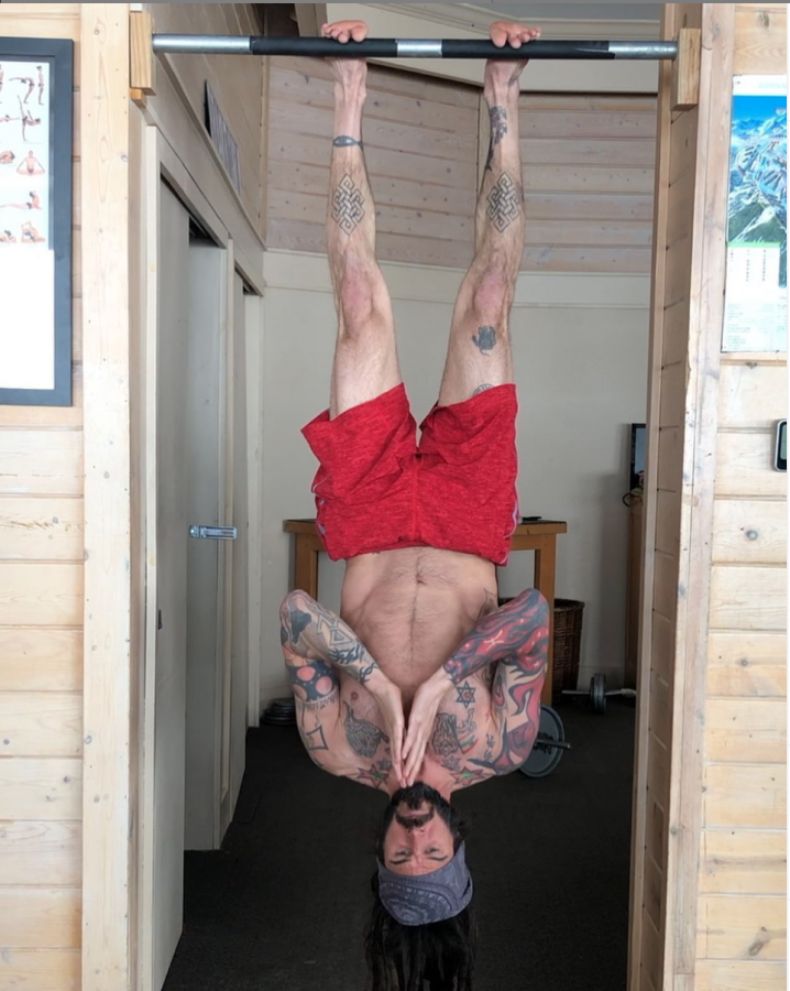 Koneval hangs upside down in an intensive yoga pose.