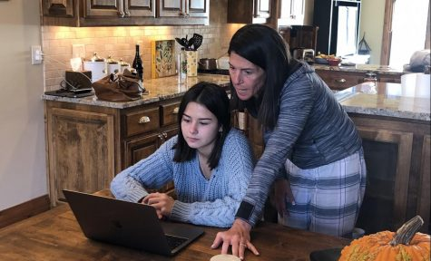 Mother, Lori Guilander, looks over her daughter Tessa's shoulder while working on October 20. They are working together at their home in Carbondale.