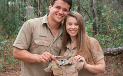 Couple Bindi Irwin and Chandler Powell expecting their first baby, holding up a little zoo keeper uniform.