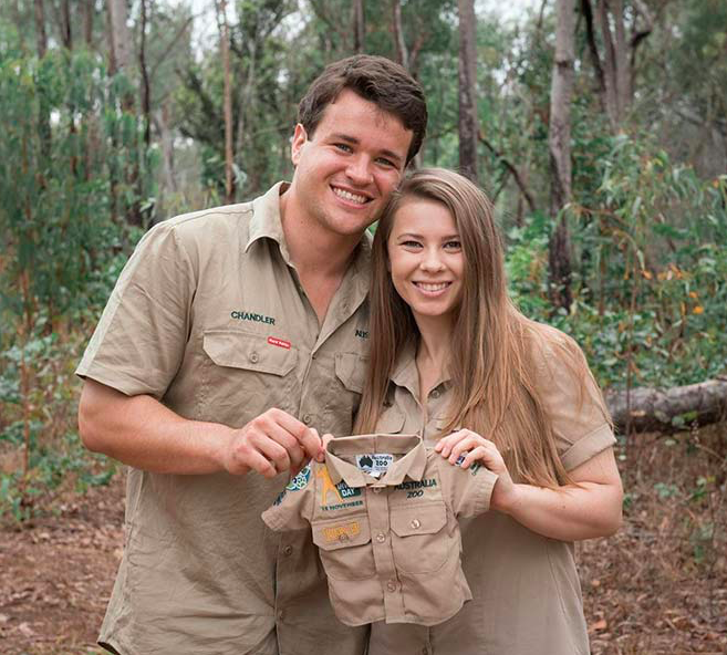Couple+Bindi+Irwin+and+Chandler+Powell+expecting+their+first+baby%2C+holding+up+a+little+zoo+keeper+uniform.