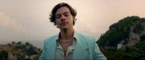"The fan favorite outfit in his new video featuring a Éliou necklace that reads ""GOLDEN"" ,the blue jacket, striped dress shirt, all by the Gucci Italian fashion house."