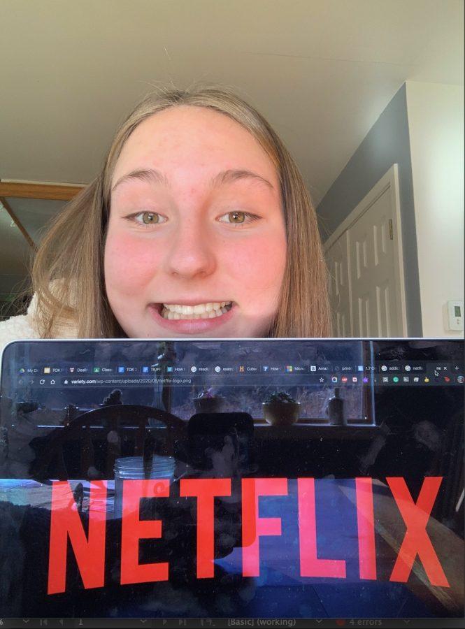 Emily Kinney, senior, smiling as Netflix opens on her computer.