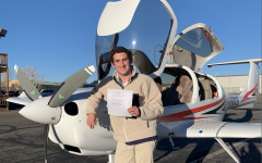 AHS junior Robert Holton posing with his new Private Pilot's license by an AHS plane.