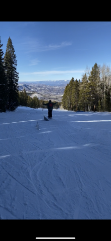 Local skier going over a box with a beautiful view in the back.
