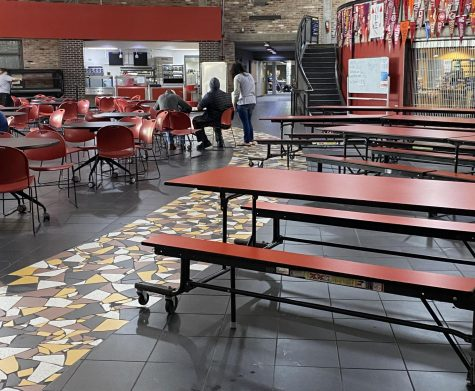 Long, red lunch tables placed on Yellow Brick Road in lunch room in an effort to create an inclusive environment
